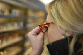 A woman tries on Warby Parker glasses at the company's traveling showroom, stationed in a school bus.